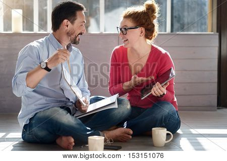 Performing results. Handsome bearded man holding notes and ginger woman tablet while sitting on floor and presenting both things.