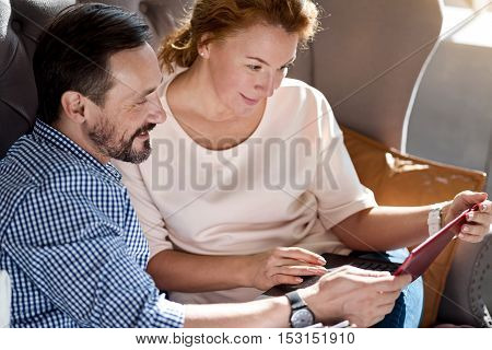Online shopping. Top view of happy adult couple using laptop together while sitting on sofa at home.