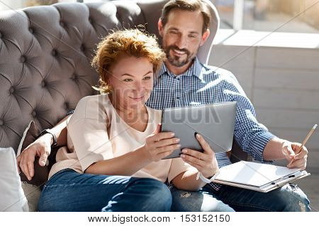 We are happy. Beautiful ginger woman lying on couch together with her bearded husband and taking selfie.