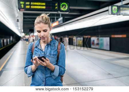 Beautiful young woman in denim shirt with smart phone, standing at the underground platform, texting