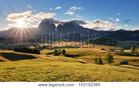 Beautiful Scenery from Alpe di Siusi Italy in summer sunrise light with small wooden cottage mountains of dolomite