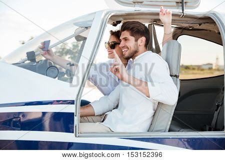 Happy smiling couple making selfie inside plane cabin after landing
