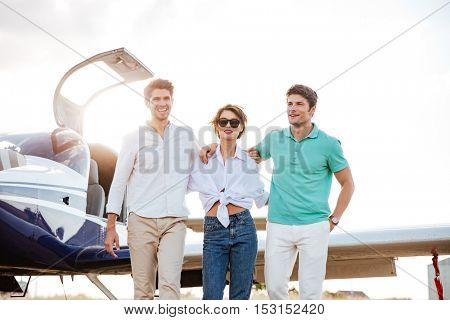 Group of happy young friends walking together on runway in airport