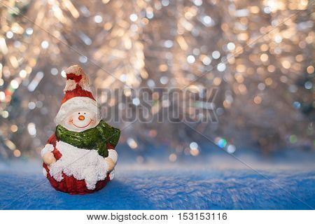 Beautiful vintage Christmas toy snowman on a background of golden bokeh. Christmas or New year background.