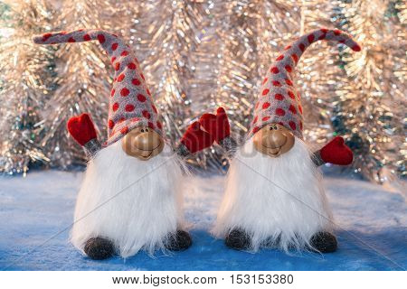 Two cheerful gnomes with hands up in red mittens and high caps on background of silver tinsel. Christmas or New Year picture.