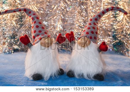 Two cheerful gnomes with  hands up facing each other on  silver background. Christmas or New Year picture.