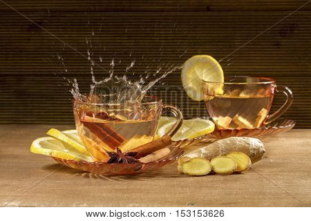 A cup of ginger tea with lemon, cinnamon and anise stars. Ginger tea on wooden background.