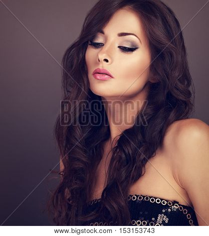 Beautiful Chic Female Makeup Model Posing With Long Curly Volume Hairstyle On Grey Background. Toned