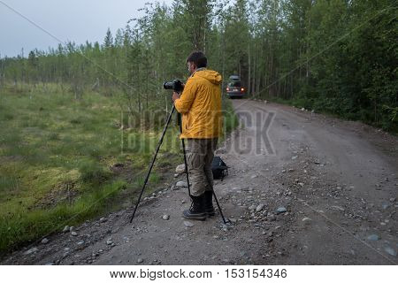 Photografer is making photos on the forest road