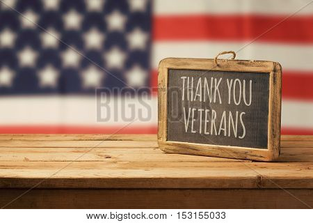 Veterans day background with chalkboard on wooden table and USA flag