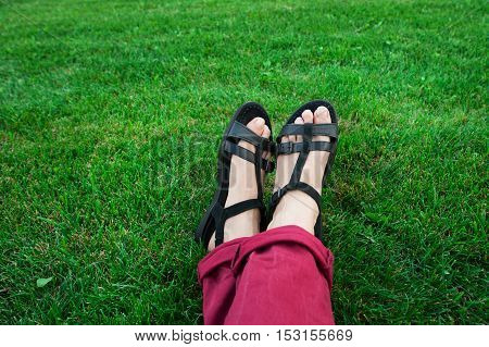 female legs in sandals on a background of green grass in a meadow.