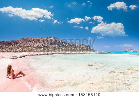 Balos lagoon on Crete island, Greece. A girl on a beach with pink sand.