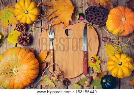 Thanksgiving dinner background with heart shape board. Autumn pumpkin and fall leaves on wooden table. View from above