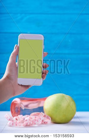 Women takes photo with smarphone with empty screen. Fresh apple, water and measurement tape - diet and fitness eating concept. On a wooden background. Shooting for social media