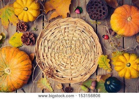 Thanksgiving dinner background with basket. Autumn pumpkin and fall leaves on wooden table. View from above