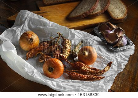 Onion, garlic and dried pepper on old paper, Vintage country table