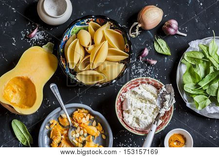 Raw ingredients for making pumpkin and ricotta stuffed shells. Pasta shells pumpkin spinach ricotta. On a dark background top view. Flat lay
