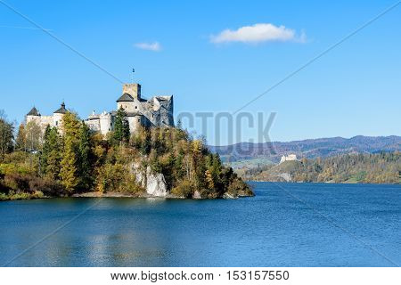 The Niedzica Castle on the Czorsztyn Lake surrounded by the beautiful autumn nature