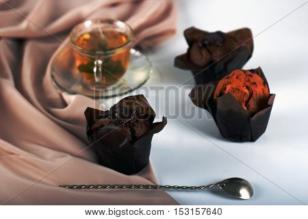 Chocolate cake with a cut piece and blade and cup of tea on gray background closeup