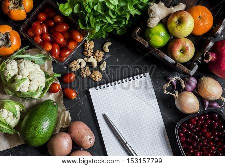 Assortment of fresh vegetables and fruit clean Notepad on a dark background. Concept of a healthy diet and planning. Top view flat lay