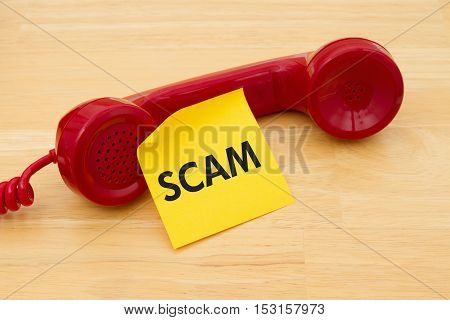 Getting a call that is an scam A retro red phone with yellow sticky note on a desk with text Scam