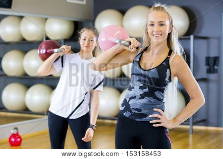 Portrait of two fit women at a fitness center. Kettlebell weight workout at the gym.