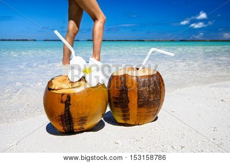 Two coconut cocktails on white sand beach with lady slim sexy legs. Vacation and travel concept