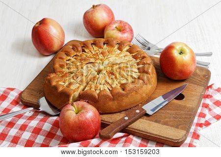 Homemade apple pie topped with slices of apples and cinnamon on white wooden table. Nearby are five red apples and knife on checkered napkin.