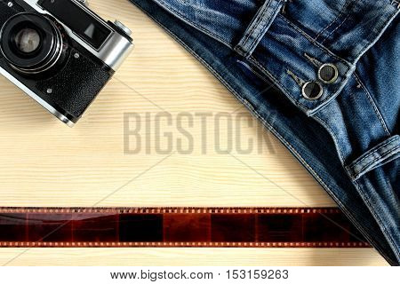 Camera film and denim pants lying on the wooden background. Youth photo equipment Photographer. The frames on the film are abstraction