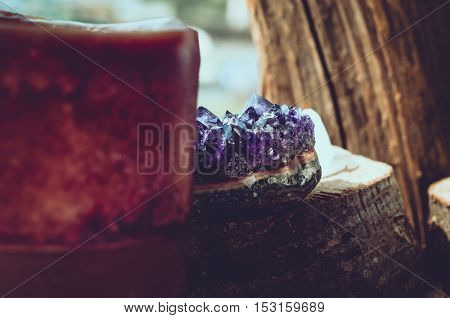 Purple and gemmy amethyst stone with brown candle on wood background as rough ametist crystals . magic stone talisman, indian mood, esoterics oriental concept.