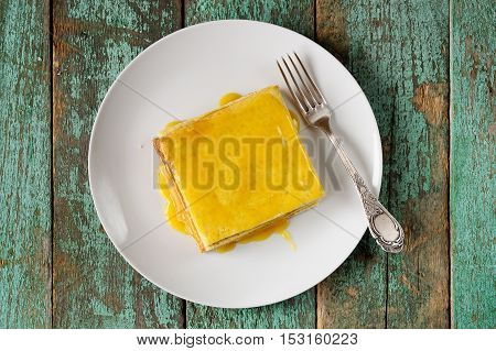 Imperfect square lemon cake and fork on white plate overhead view