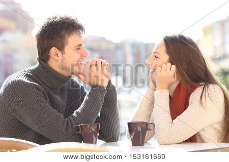 Side view of a happy couple dating and flirting in love looking each other in a bar terrace with a port of urbanization in the background