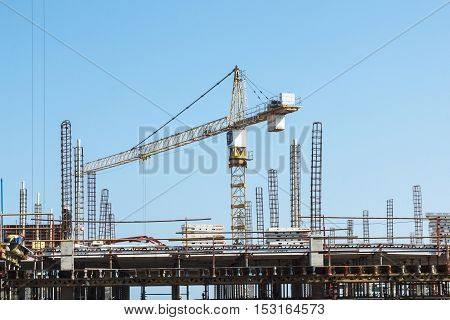 MHLANGA RIDGE DURBAN SOUTH AFRICA - OCTOBER 21 2016: High lift crane and many unknown people wokling amongst scaffolding and concrete structures with reinforcing bars extending above work area