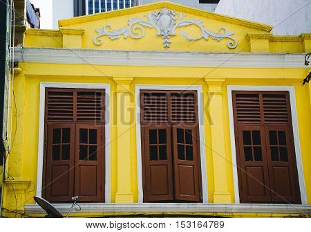 Photo of the Old yellow building facade with three shutters and stucco work. City architecture. Cultural heritage