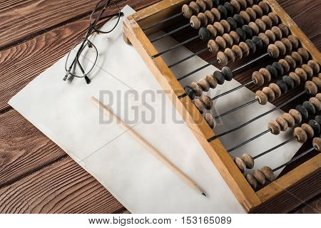 Vintage abacus envelopes, glass and paper on wooden table