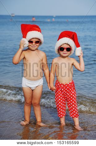 Children in red Santa Claus hats and sunglasses on the background of the sea