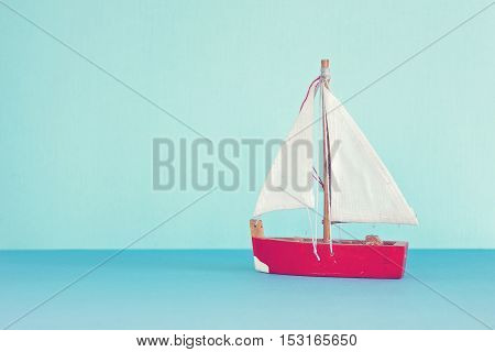 Vintage sailboat resting on blue waters with blue background