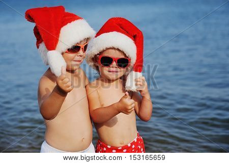 Portrait of children in red Christmas caps and sunglasses on the background of the sea. Winter holiday in the sea.