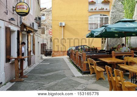 Senj Croatia - September 18 2016: a small town in northern Croatia located on the Adriatic coast. Tavern in the old town. At the door stands a waitress, in a restaurant garden sits two guests. In the background you can see another pub.