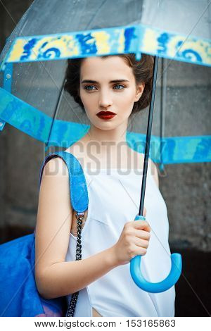 young woman with retro hair, with a blue backpack and umbrella, beautiful makeup, a white shirt and a pink shorts