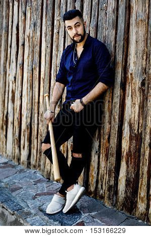 handsome young man in dark blue shirt with beat standing near wooden wall