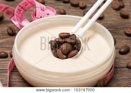 Cellulite busting product. Anti-cellulite cosmetics with caffeine. Jar of cream with coffee essential oil, spoon of coffee beans, body measuring tape on wooden surface. Closeup, shallow depth of field