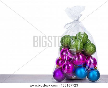 Christmas balls in plastic bag on wooden board and white background