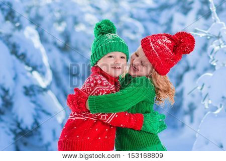 Little girl and boy in red and green knitted hat catching snowflakes in winter park on Christmas eve. Kids play outdoor in snowy winter forest. Children catch snow flakes on Xmas. Toddler kid playing.