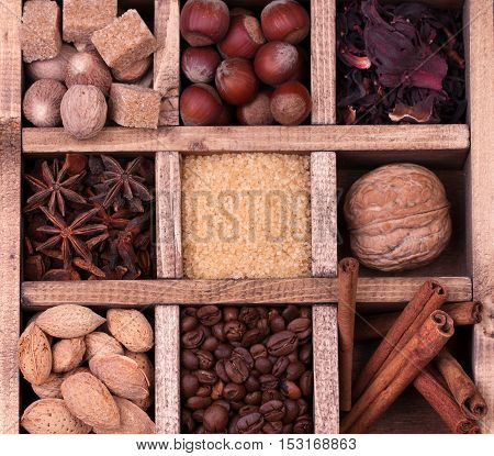 Coffee and spices in a wooden printers box. Coffee beans, anise stars, brown sugar, walnut, hazelnut and nutmeg.