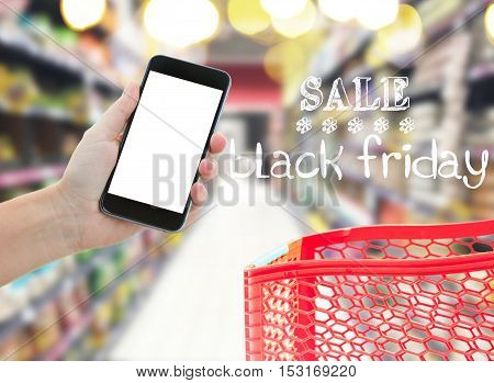 hands holding mobile smart phone with copy space on empy screen in comercial center blur background and black friday sale words