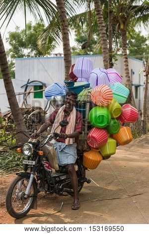 Dindigul India - October 22 2013: A smiling man an ambulant vendor drives up on his motorcycle at a rural village. The bike is overloaded with colorful plastic jars the size of five to ten liters.