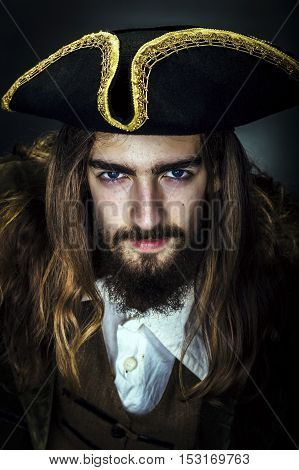 Portrait of a medieval bearded pirate on black background.