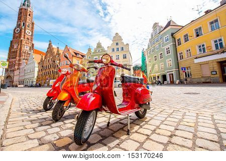 Landshut, Germany - July 04, 2016: Retro red Vespa scooters on the street in Landshut old town in Germany.