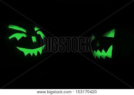 Two Green Halloween Pumpkins On Black Background